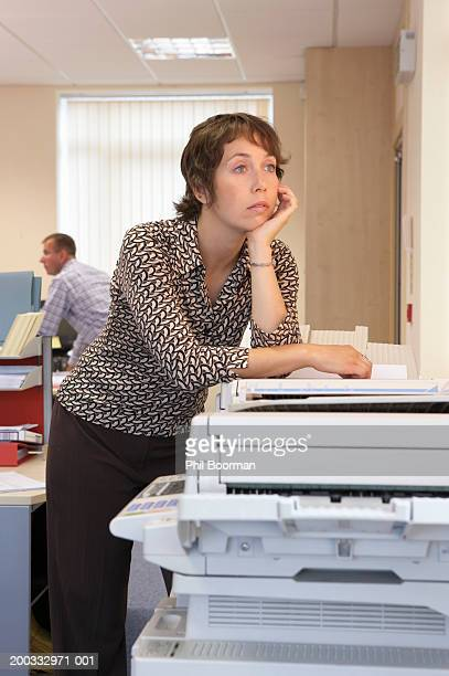 Woman leaning on photocopier in office, chin in hand