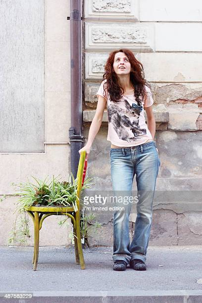 Woman leaning on plant chair looking up