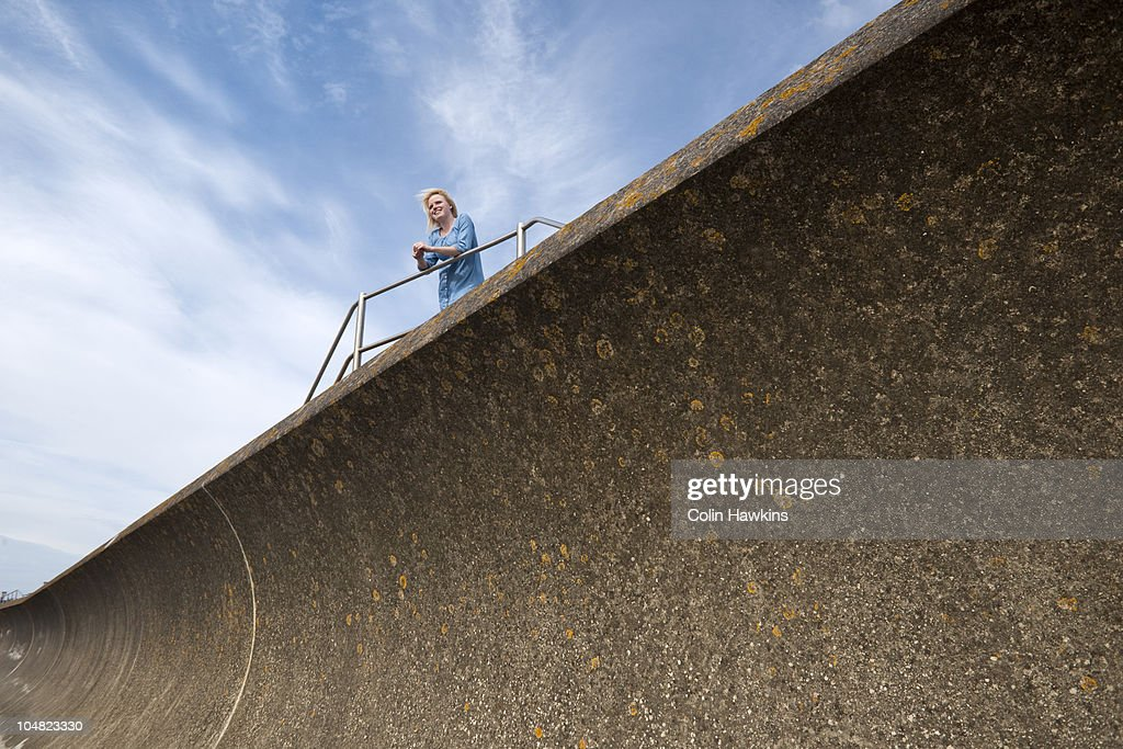 Woman leaning on rail above wall : Stock Photo