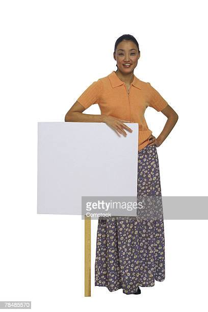 Woman leaning on sign