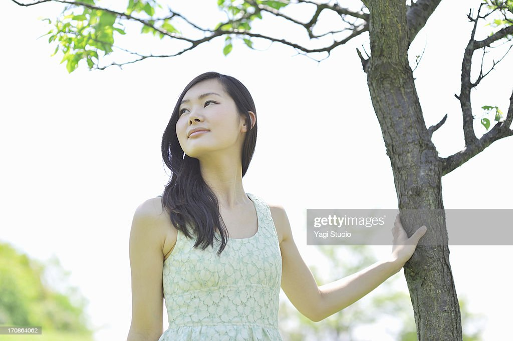 Woman leaning on tree in nature. : Stock Photo