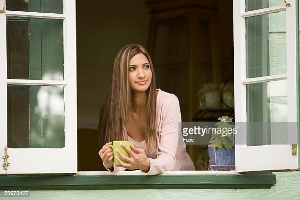 Woman leaning on windowsill