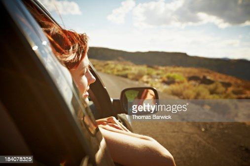Woman leaning out front window of car