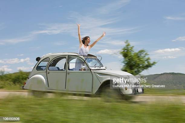 Woman leaning out of a driving car