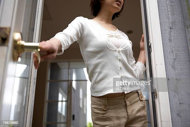 Woman leaning out of open door of home