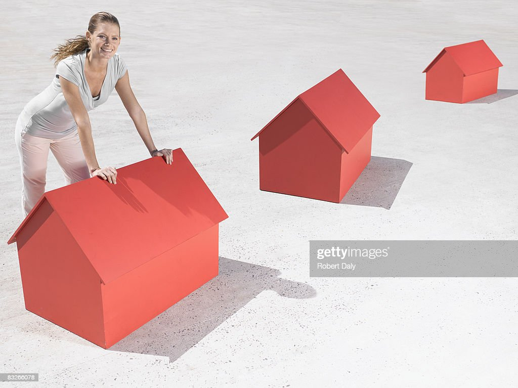 Woman leaning over model houses : Stock Photo