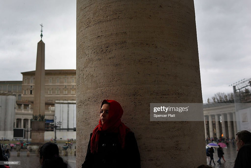 A woman leans against a column as she waits in St. Peter's Square on March 12, 2013 in Vatican City, Vatican. Pope Benedict XVI's successor is being chosen by the College of Cardinals in Conclave in the Sistine Chapel. The 115 cardinal-electors, meeting in strict secrecy, will need to reach a two-thirds-plus-one vote majority to elect the 266th Pontiff.