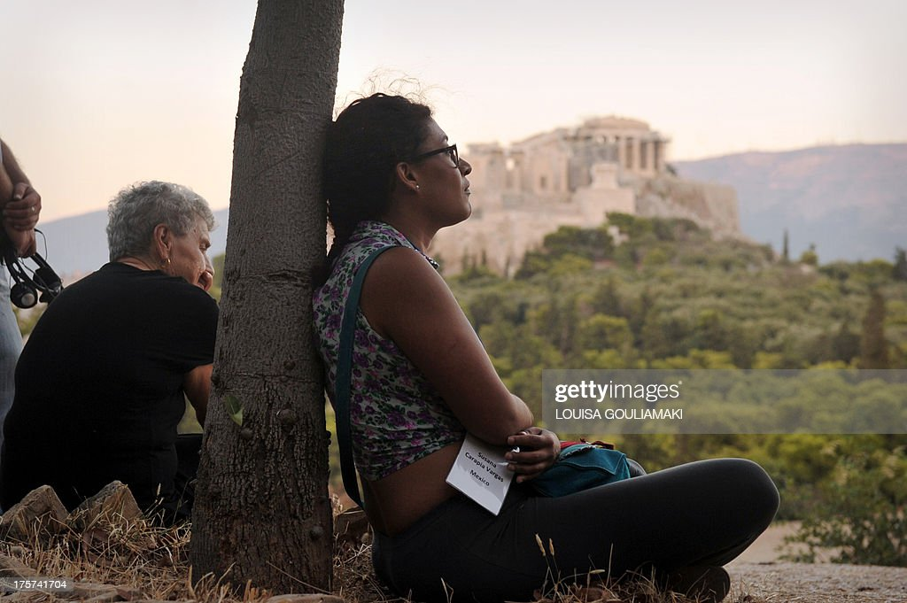 A woman leans against a tree as she listens to a speech by a philosopher during the XXIII World Philosophy Congress Pnyx special plenary session at the Pnyx hill opposite the ancient Acropolis in Athens on August 7, 2013. Greece, widely considered as the birthplace of western philosophy, hosts the 23rd World Congress of Philosophy, organised by the International Federation of Philosophical Societies (FISP), which runs until August 10.