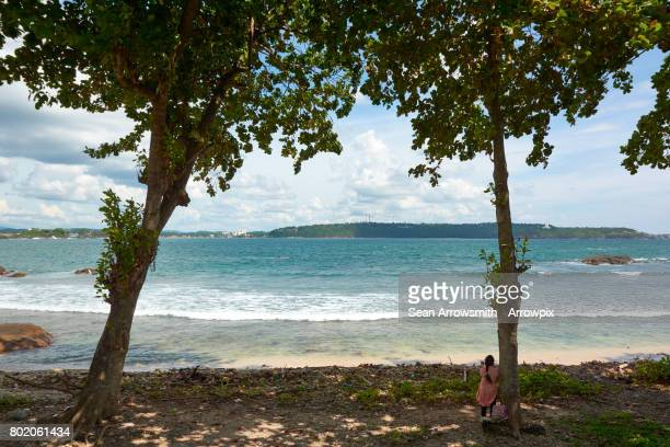 Woman leans against tree at beach