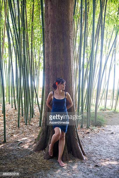 Woman leans against tree trunk in bamboo forest