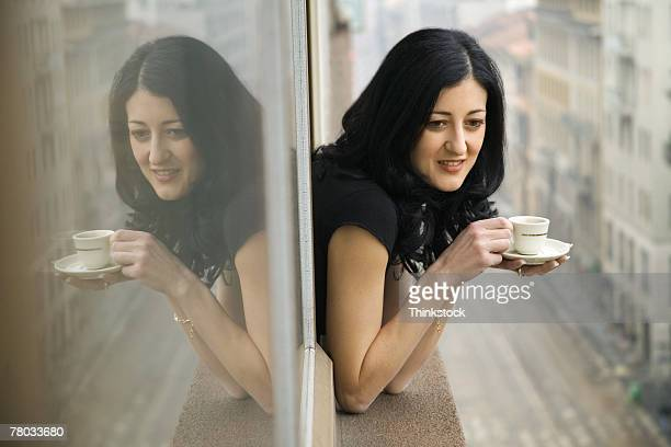A woman leans out of a window drinking a cup of espresso as she watches over a street in Milan, Italy.