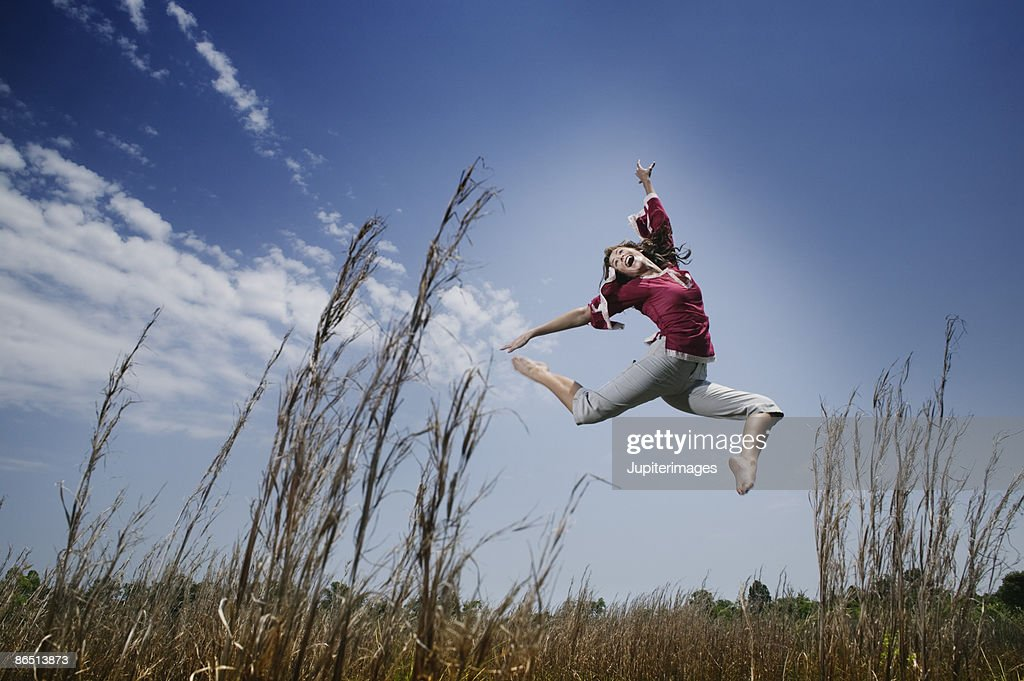 Woman leaping in field : Stock Photo