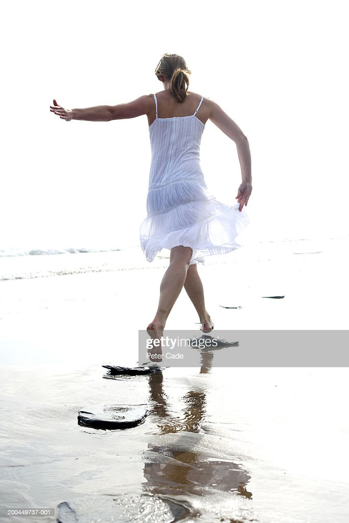 Woman leaping on stepping stones at beach, rear view
