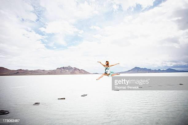 Woman leaping over gap in stone pathway on lake