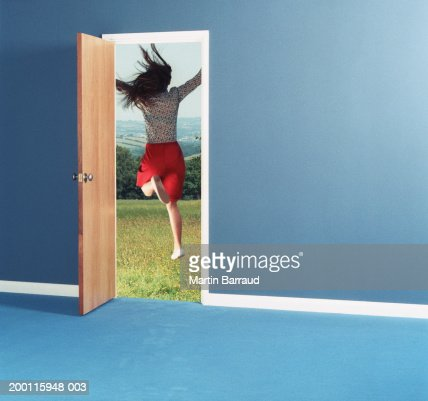 Woman leaping through doorway into field, rear view : Stock Photo
