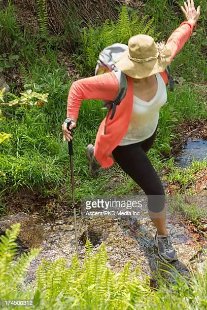 Woman leaps across creek while hiking