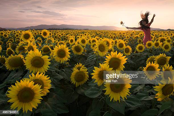A woman leaps for joy in a field of sunflowers during sunset.