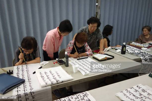 Woman learn and practice korean calligraphy at the Korean Community Services center on August 10 in New York Most of those at the center said they...