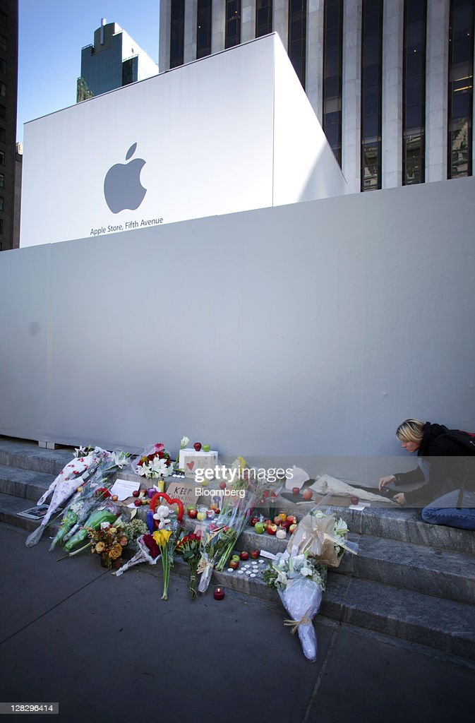 A woman leaves a bouquet of flowers at a memorial for Steve Jobs, co-founder and former chief executive officer of Apple Inc., outside an Apple store in New York, U.S., on Thursday, Oct. 6, 2011. Jobs, who built the world's most valuable technology company by creating devices that changed how people use electronics and revolutionized the computer, music and mobile-phone industries, died. He was 56. Photographer: Stephen Yang/Bloomberg via Getty Images