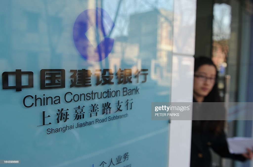 A woman leaves a branch of the China Construction Bank in Shanghai on March 25, 2013. China Construction Bank, one of the country's top four lenders, said its net profit rose 14.1 percent year-on-year in 2012, lifted by growth in net interest income. AFP PHOTO / Peter PARKS