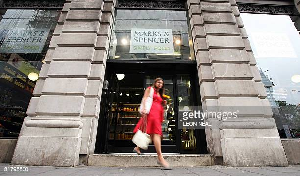 A woman leaves a Marks and Spencer store at Green Park tube station in London on July 2 2008 British retailer Marks and Spencer shares tumbled by...
