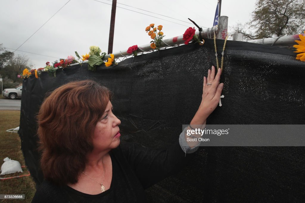 A woman leaves a rosary at the First Baptist Church of Sutherland Springs on November 12, 2017 in Sutherland Springs, Texas. The congregation held service today in a tent on the towns ball park. Today the original church will open to visitors as a memorial to the victims who were shot during last Sunday's service. Residents of the community are still trying to heal following the shooting. Devin Patrick Kelley shot and killed the 26 people and wounded 20 others when he opened fire during Sunday service at the church.
