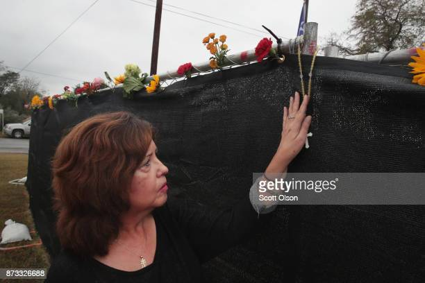 A woman leaves a rosary at the First Baptist Church of Sutherland Springs on November 12 2017 in Sutherland Springs Texas The congregation held...