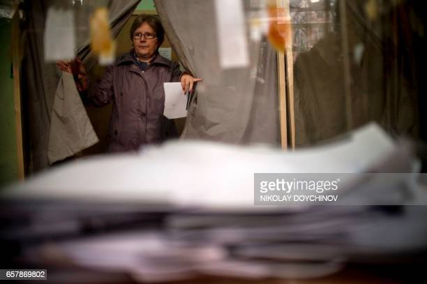 A woman leaves a voting booth before casting his ballot at a polling station in Sofia on March 26 during the country's parliamentary election...