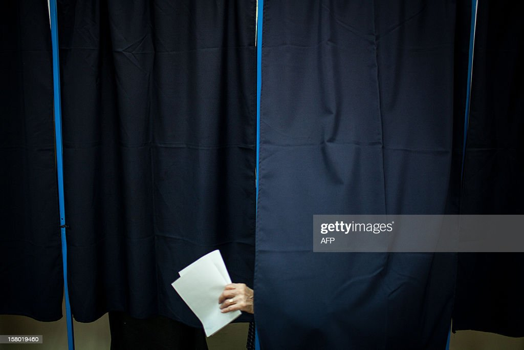 A woman leaves a voting cabin with her ballot at a polling station in Bucharest, Romania on December 9, 2012 as Romanians head to the polls to elect a new parliament. The centre-left ruling coalition of Prime Minister Victor Ponta is on course for a large victory, an outcome that would create a bitter cohabitation with centre-right President Traian Basescu.