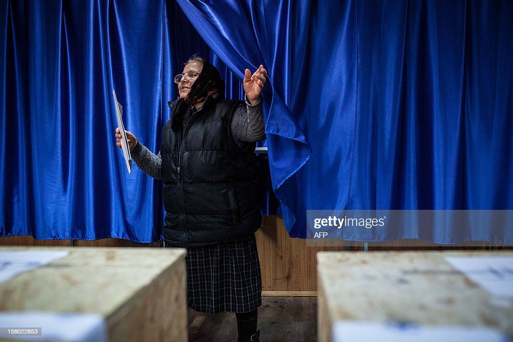 A woman leaves a voting cabin with her ballot at a polling station in Bucharest, Romania on December 9, 2012. Austerity-weary Romanians voted for a new parliament Sunday, with the centre-left ruling coalition on course for a large victory that was likely to trigger fresh tension between the party and rival president Traian Basescu.