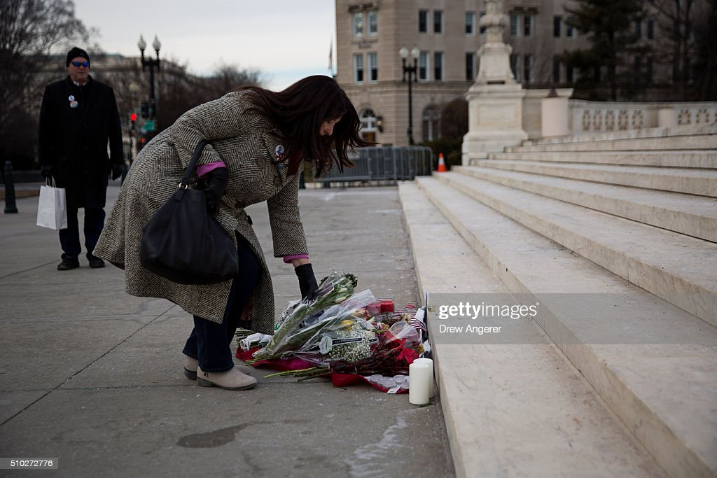 A woman leaves flowers at a makeshift memorial for Supreme Court Justice Antonin Scalia at the U.S. Supreme Court, February 14, 2016 in Washington, DC. Supreme Court Justice Antonin Scalia was at a Texas Ranch Saturday morning when he died at the age of 79.