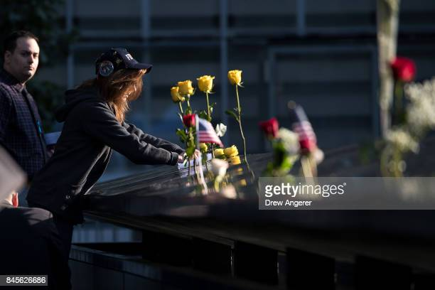 A woman leaves flowers at the North pool memorial site before a commemoration ceremony for the victims of the September 11 terrorist attacks at the...