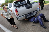LAREDO TX A woman leaves her vehicle as a agent inspect the undercarriage of her car for bulk cash at the port of entry in Laredo TX July 27 2010 US...