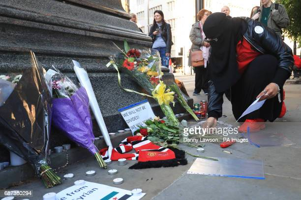 A woman leaves tributes in Albert Square outside Manchester Town Hall after a 23yearold man was arrested in connection with the Manchester concert...