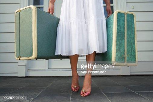 Woman leaving entrance door carrying two suitcases, low section : Foto stock