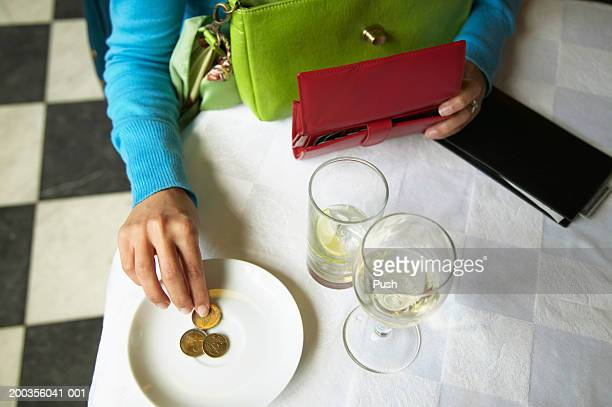 Woman leaving tip in restaurant, overhead view