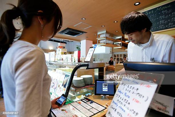 A woman left demonstrates the use of PayPal Inc's mobile payment application on an Apple Inc iPhone while an employee checks the transactions on an...