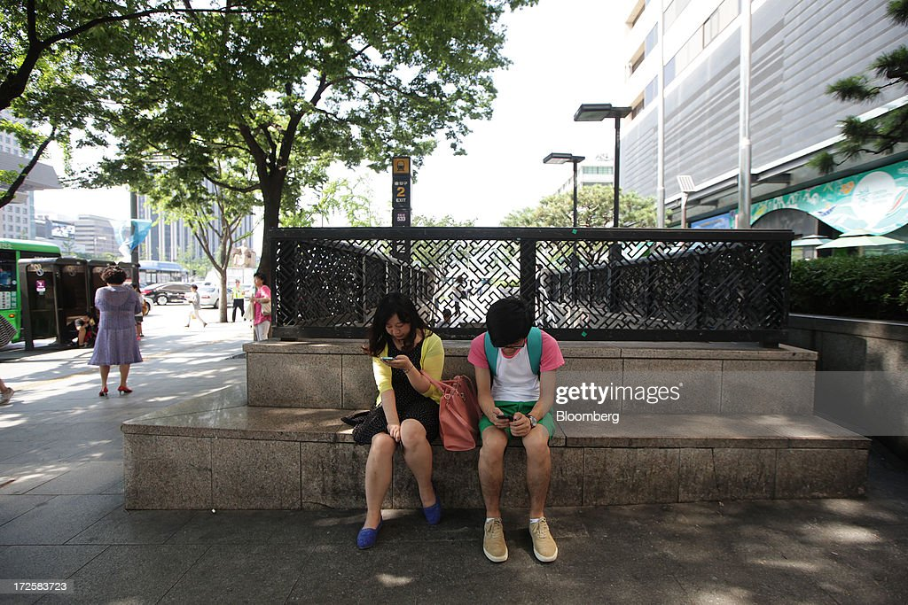 A woman, left, uses an Apple Inc. iPhone next to a man using a Samsung Electronics Co. smartphone as they sit outside a subway exit in Gwanghwamun Square in Seoul, South Korea, on Wednesday, July 3, 2013. Samsung Electronics lost $25.3 billion in market capitalization last month, more than the value of competitor Sony Corp., as sales of its flagship Galaxy S4 smartphone fell short of investor expectations. Photographer: Woohae Cho/Bloomberg via Getty Images