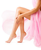 Woman Legs Body Beauty in Pink Cloth Fabric, Girl Leg Smooth Skin on White background