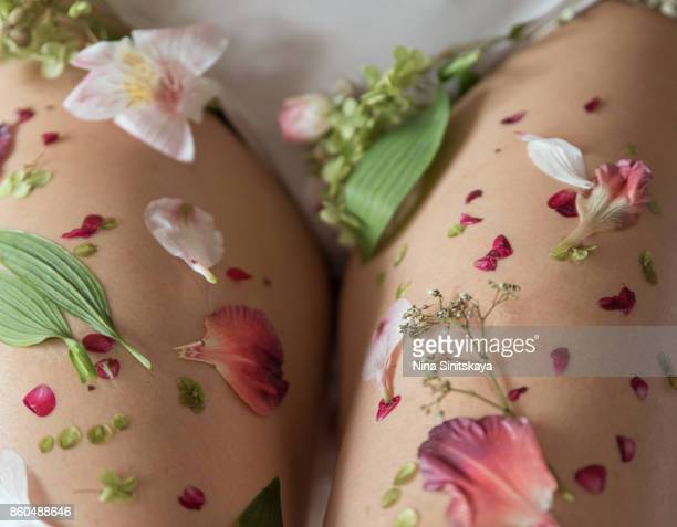 Woman legs covered with flower petals