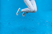 Jumping woman legs in blue sneakers against  blue wall background