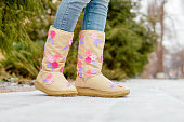 Funny legs in boots with flowers and snow