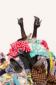 Woman buried under an untidy cluttered woman wardrobe, clothes and accessories.  Woman in high heels needs help from to much shopping. Shopaholic girl.