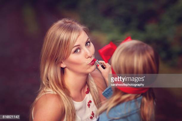 woman letting a little girl apply her make up