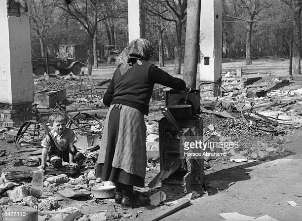 A woman liberated by the 7th Army from slave labour in Germany cooks a meal for herself and her child at Wurzburg