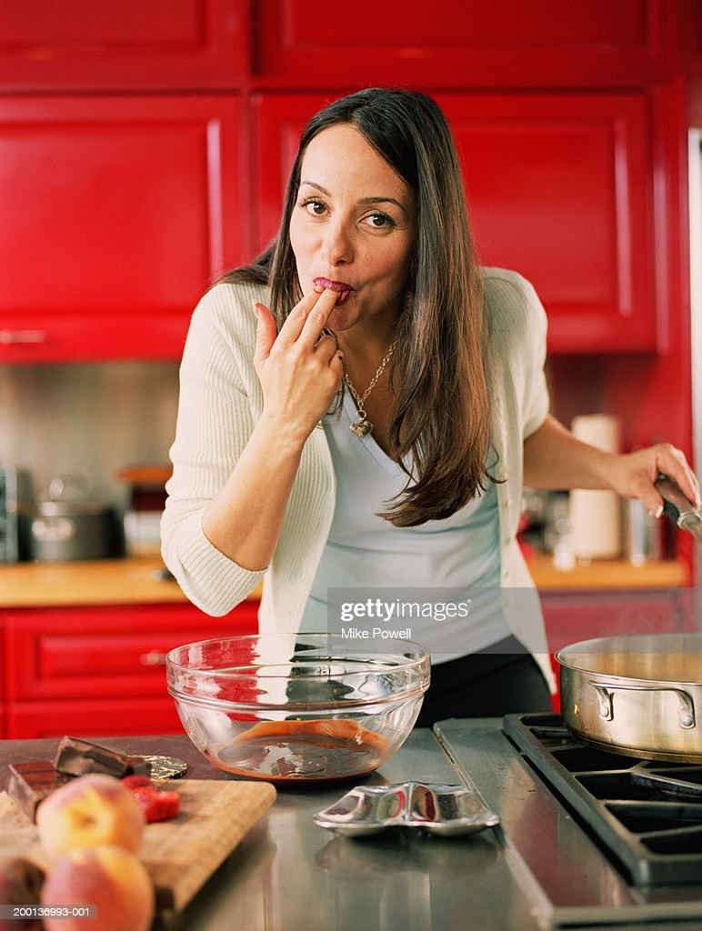 Woman licking chocolate from fingers in kitchen : Stock Photo