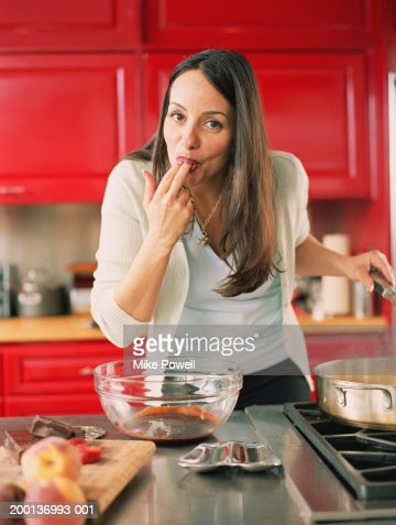 Woman licking chocolate from fingers in kitchen : ストックフォト