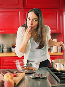 Woman licking chocolate from fingers in kitchen