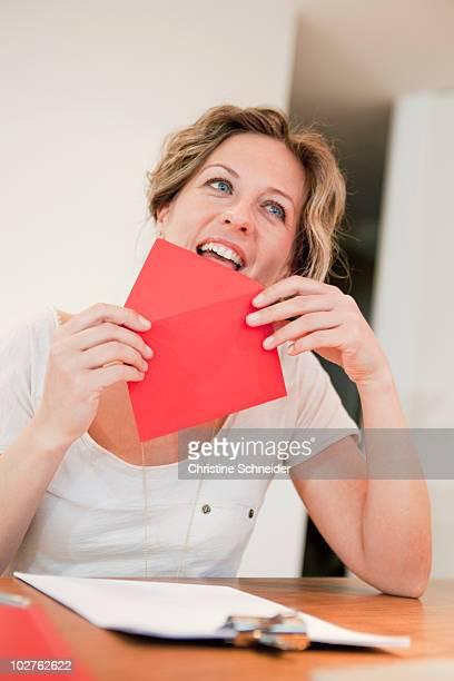 Woman licking on red envelope