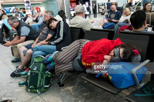 A woman lies across several chairs as she sleeps at Heathrow Airport Terminal 5 on May 28 2017 in London England Thousands of passengers face a...